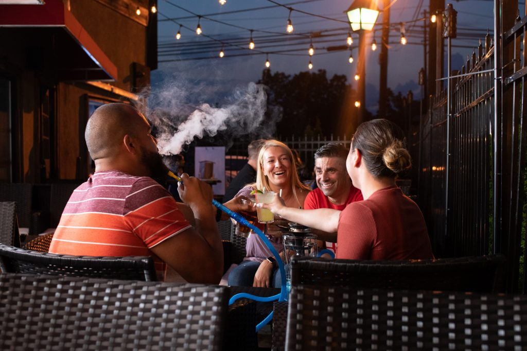Rob the owner outside by the patio with his friends smoking hookah and laughing